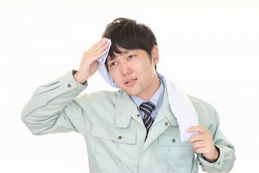 一個穿著工作服的男人,看上去很疲倦