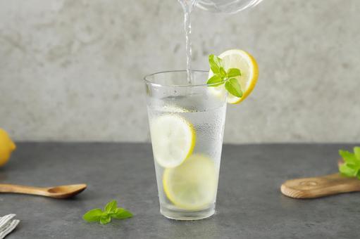 將檸檬水倒入玻璃杯中