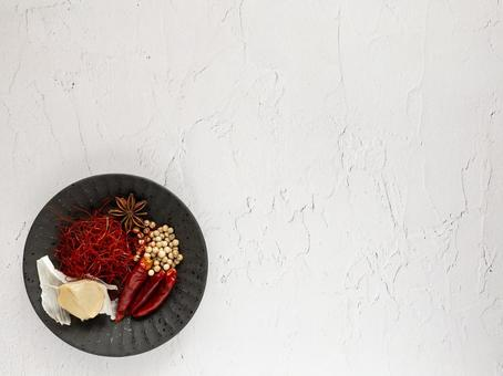 Red pepper and garlic on a small black plate on a white background