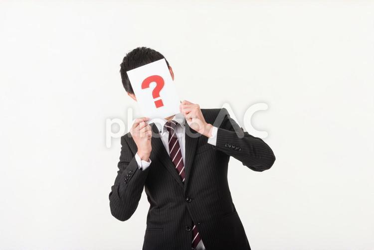 クエスチョンマークで顔を隠すビジネスマン3の写真