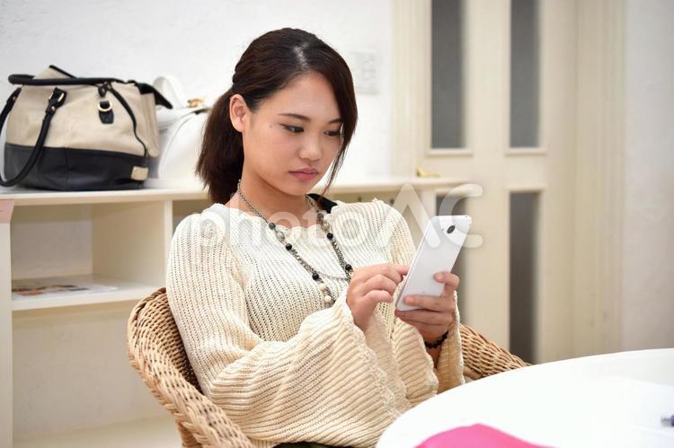 スマホを操作する女子高生の写真