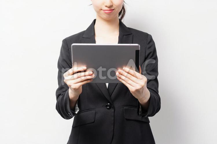 白バックの前に立って、タブレット端末を使うビジネスウーマンの写真