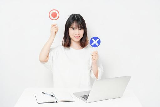 A young woman holding an OK and NG placard while using a laptop in front of a white background