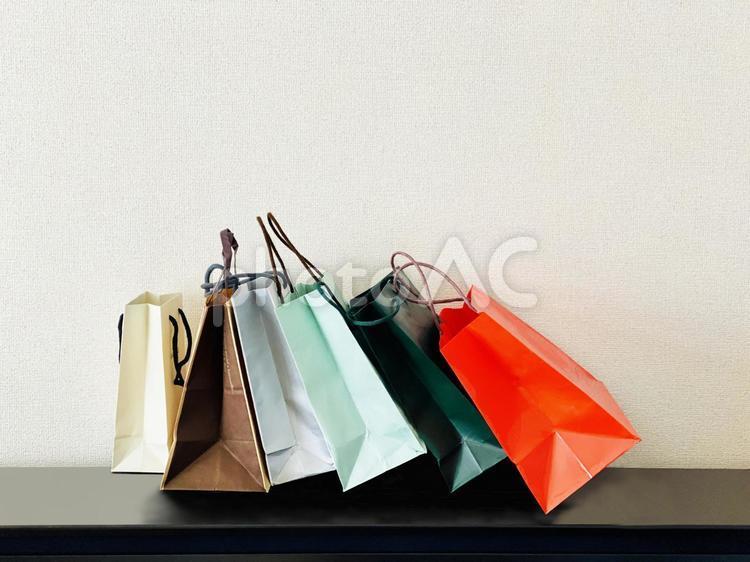 たくさんのショッピングバッグが倒れかかるテーブルの写真