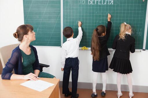 小学学生在黑板上写6