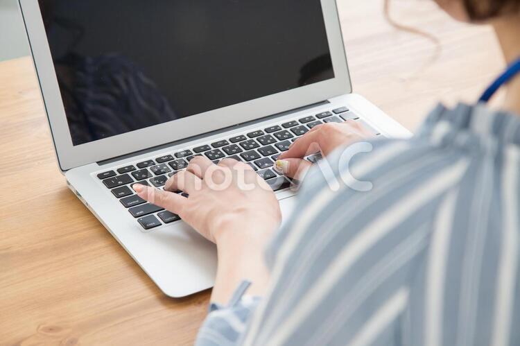 パソコンを打つ女性の写真