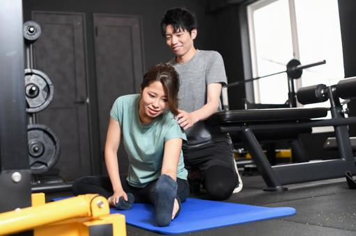 Asian women stretching and male trainers assisting