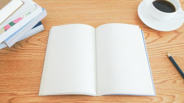 木紋桌上打開筆記本的學習影像資料(有咖啡、鉛筆、堆放的書)
