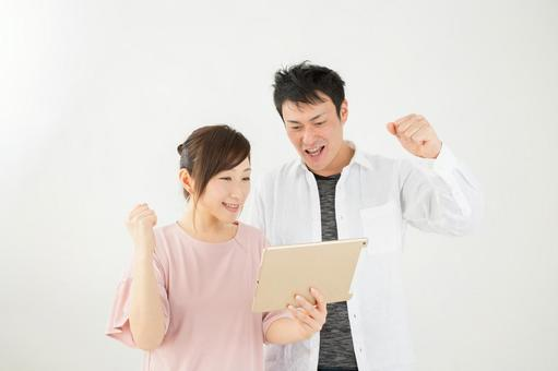 A man and a woman exciting when looking at a tablet