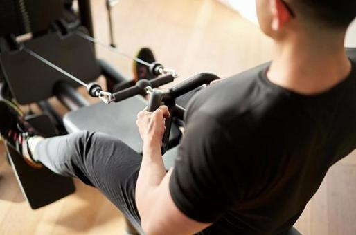 Asian man training on a low pulley machine