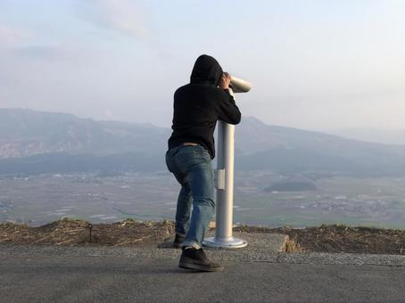 A man looking into a telescope