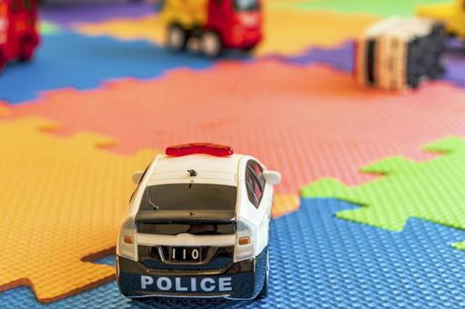 Vehicle toys cluttered on colorful mats