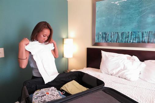 A woman loading and unloading a suitcase in a hotel room