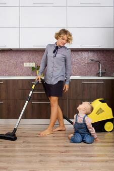 Working mother with a son and a vacuum cleaner that imitates cleaning 15