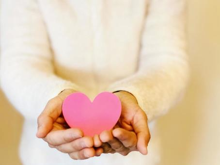 A woman holding a heart in both hands