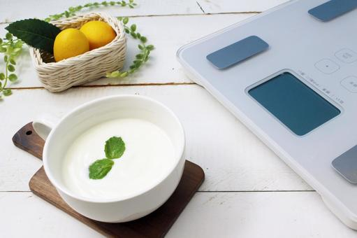 Lemon, yogurt and scale on a white wooden table