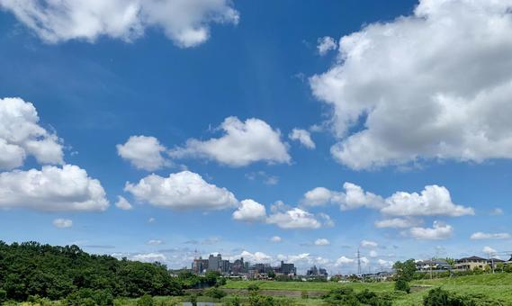 Summer clouds, greenery and distant city