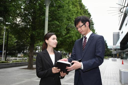 A businessman looking at a notebook, business woman 1