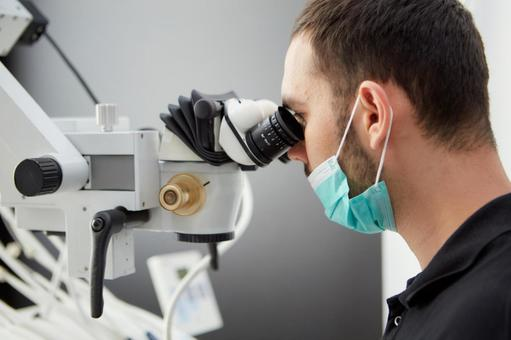 Male dentist with microscope treatment 2