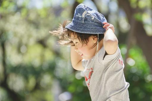 A child whose hat is about to be blown off by a strong wind