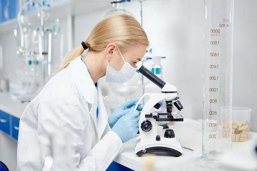 Researcher looking through a microscope 6