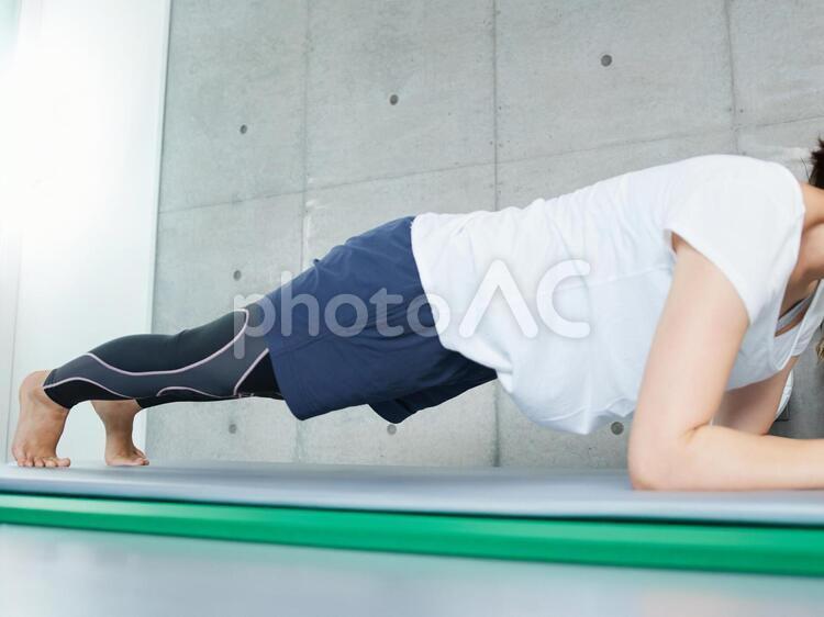 自宅でプランクのトレーニングをする日本人女性の写真