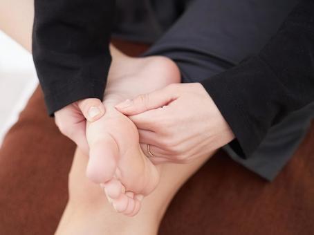 Japanese woman doing a self-massage of her feet