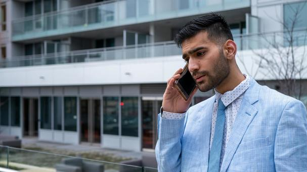 진지한 표정으로 전화를 양복을 입은 비즈니스맨