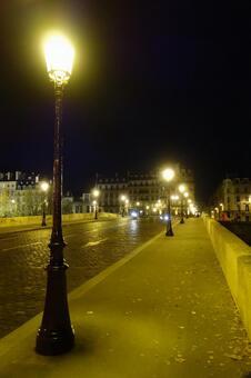 The sidewalk of Paris illuminated by street lights