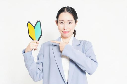 A woman standing in front of a white background and holding a beginner mark
