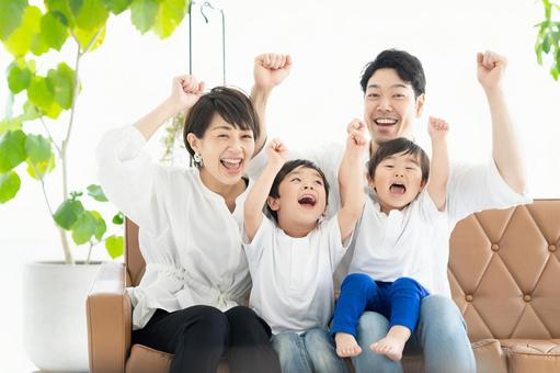 Image of parents and children watching TV with their hands raised