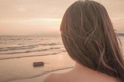 황혼의 해변과 검은 머리의 여자