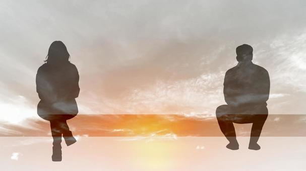 Male and female silhouette sitting away from a chair_sunset background