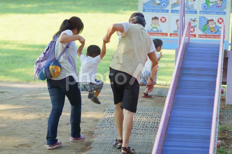 滑り台で遊ぶ家族の写真
