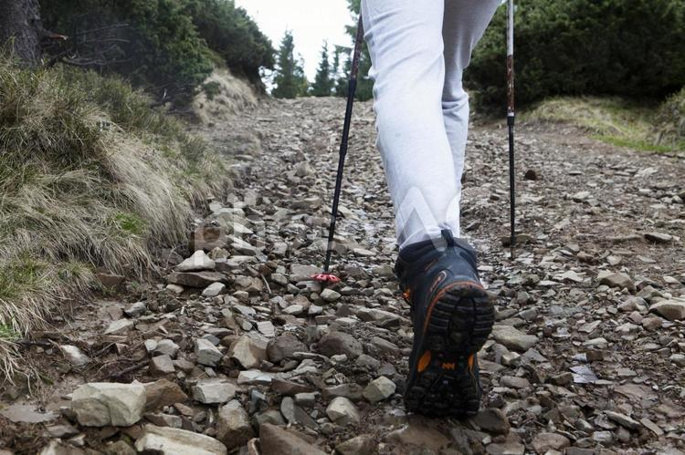石の多い道を歩く男性トレッカーの足元1の写真