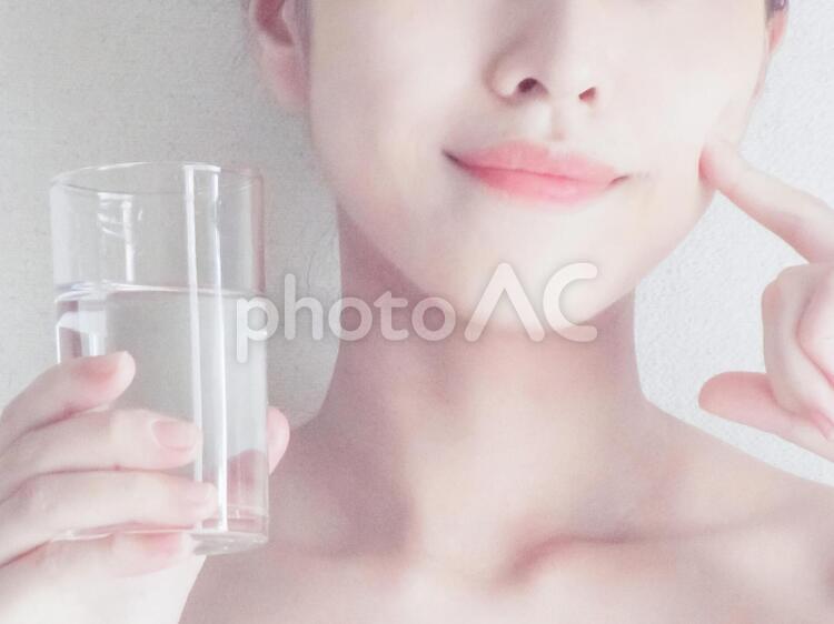 水を飲みながら頰に指を当てる女性の写真