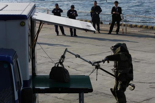 대테러 훈련 전시에서 X 선 검사 차량에 의심 물질을 싣는 경찰관