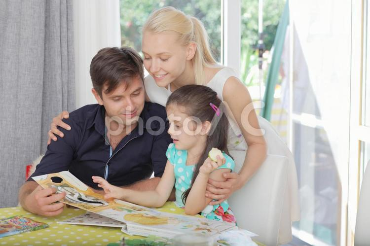 女の子に絵本を読み聞かせる男性と肩を抱く女性4の写真