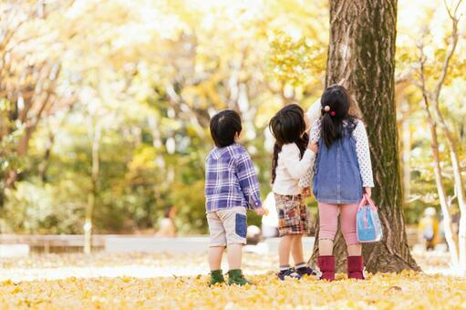 Three children playing in the autumn park