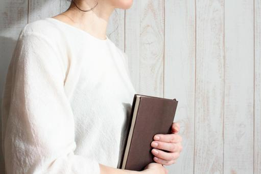 A woman holding a notebook in her chest