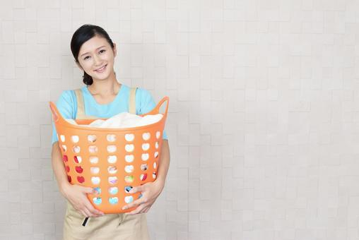 A smiling woman with a laundry basket