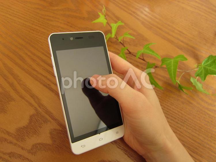スマートフォンを持つ手2の写真