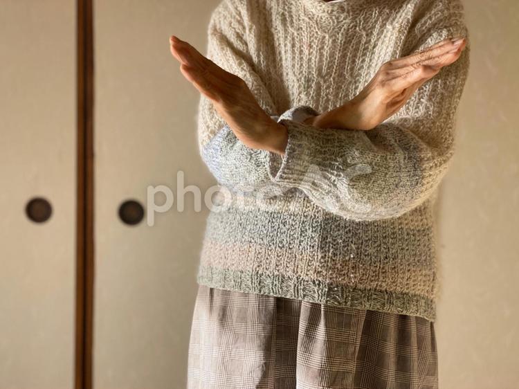 両手でバツをする高齢者の写真