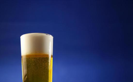 Cold beer in a glass with a blue background in the background