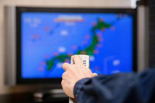 A man watching the weather forecast on TV