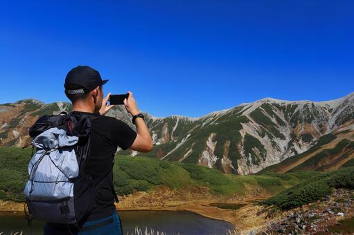 스마트 폰에서 산을 촬영하는 등산객