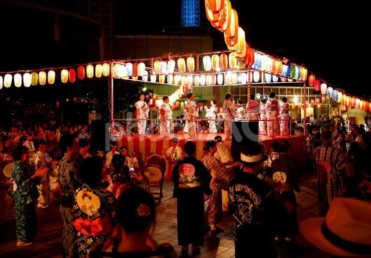 Many Japanese gathering dancing around Yagura (a turret).