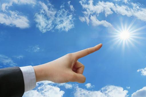 Businessman pointing to a goal-blue sky and sun