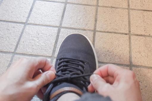 신발 끈을 묶는 손
