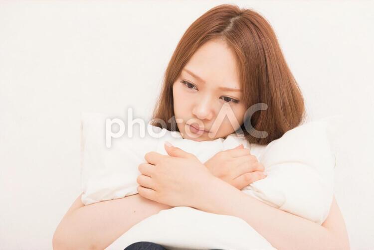 クッションを抱えて考える女性2の写真